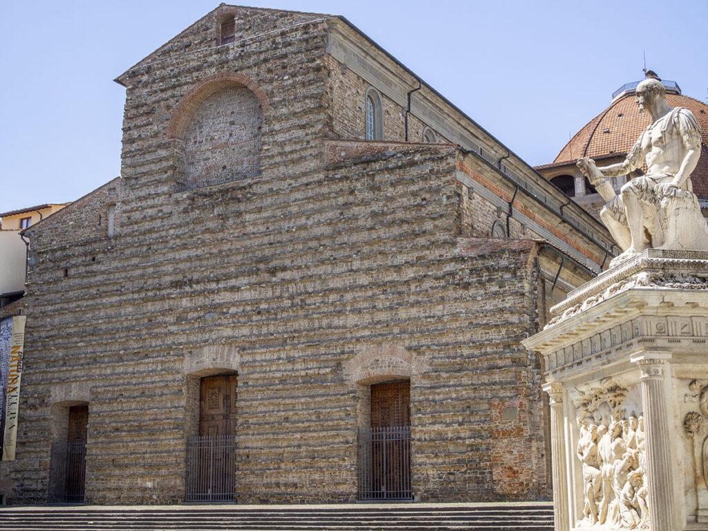 Bazylika Świętego Wawrzyńca z nagą, kamienną fasadą. Projekt fasady autorstwa Michała Anioła nigdy nie został zrealizowany, polski przewodnik po Florencji